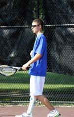 Boy walking with tennis racket